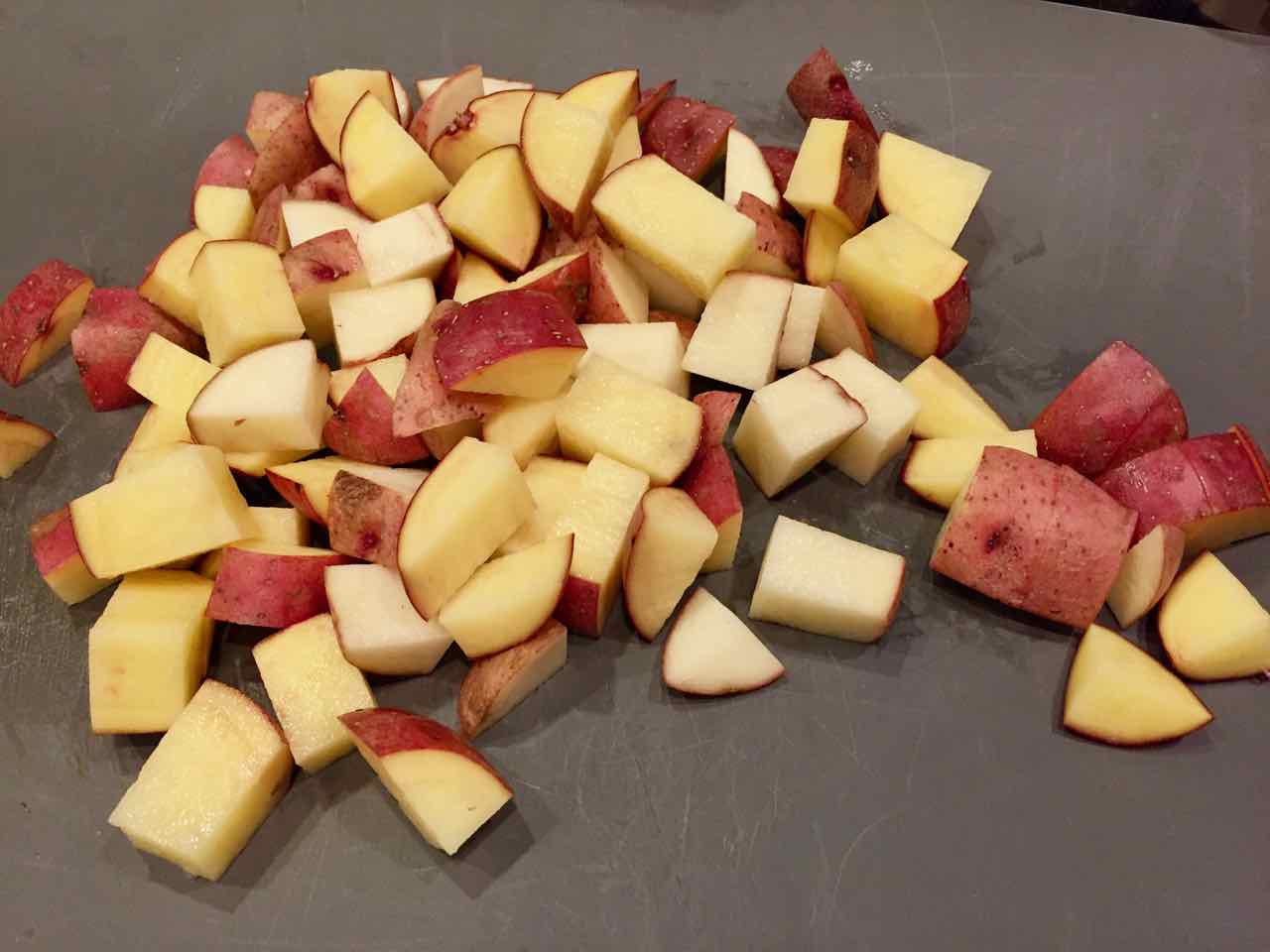 Image of chopped red potatoes on a cutting board.