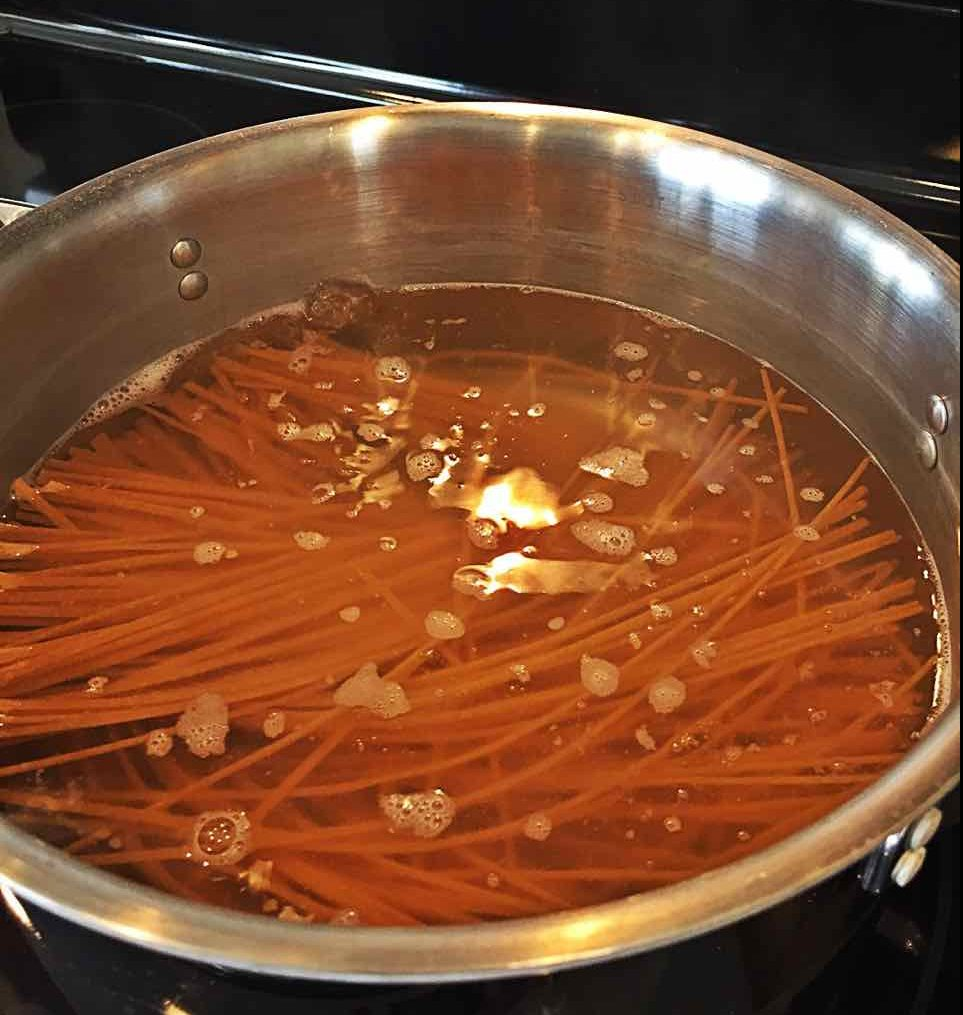 Image of linguini pasta boiling in a pot of water on the stove.